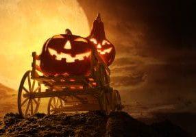 Halloween pumpkins on farm wagon at spooky in night of full moon.