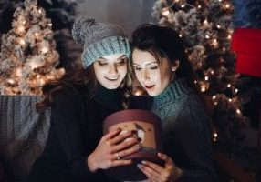 Two girlfriends opening and holding together rounded box with present, looking inside with opened mouth. Women surprised looking and giving gifts. Merry Christmas and happy new year.